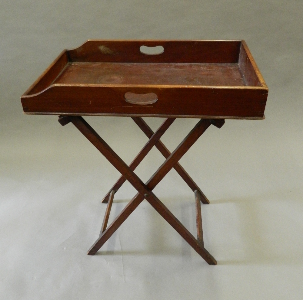 Lot 904 - A Victorian mahogany butlers tray on stand. 65 cm long.
