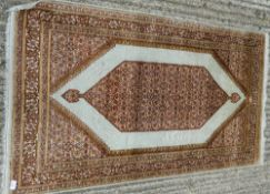 A small silk ground rug and another.