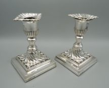 A pair of silver square based candlesticks, hallmarked Sheffield 1895. 12 cm high.