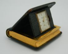 A mid 20th century travelling clock in the form of a book, green leather, Made in USA. 6 cm high.
