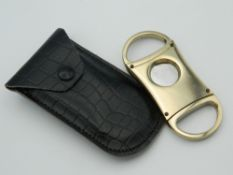 A cased cigar cutter. 8 cm long.