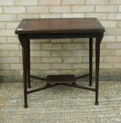 An Edwardian swivel top mahogany games table. 71 cm wide.