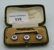 A boxed set of buttons and a stock pin