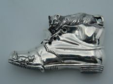 A vesta depicting a cat in a boot. 6 cm long.