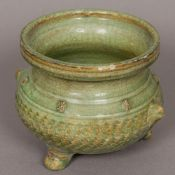 A Chinese celadon glaze porcelain censer, of squat baluster form, with twin mask handles.