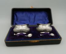 A cased pair of silver salts. Case 19 cm wide (1.