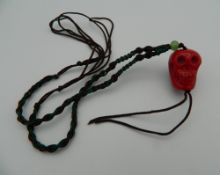 A coral skull pendant. 2.5 cm high.