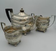 A Georgian three piece silver tea set. The tea pot 28.5 cm long (32.6 troy ounces total weight).