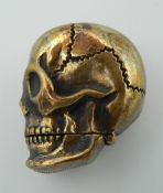 A brass vesta formed as a skull. 4 cm high.