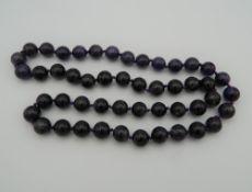 An amethyst bead necklace. 66 cm long.