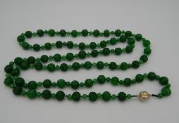 An apple green jade necklace, set with a bi-coloured 18 K gold clasp. 140 cm long.