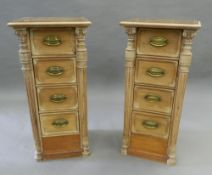 A pair of small banks of pine drawers with leather tops. 80.5 cm high.