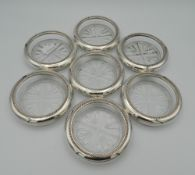 Seven glass and sterling silver rimmed coasters, stamped sterling. Each 9.5 cm diameter.
