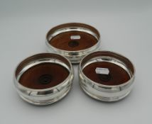 A trio of silver and wood coasters,