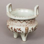 A Chinese porcelain censer Of typical squat circular form with twin loop handles,