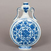 A Chinese blue and white porcelain moon flask Of typical form, with twin scrolling handles,