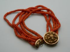 A string of coral beads with an unmarked 18 ct gold clasp. 43 cm long.