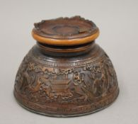 A 19th century Chinese carved coconut cup, mounted on a wooden stand. 7 cm high.