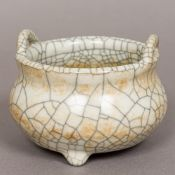 An antique Chinese crackle glaze censer Of squat circular form with twin loop handles,