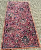 A red ground Persian wool rug. 246 x 125 cm.