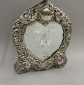 A silver framed heart shape mirror. 27 cm high.