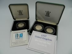 A pair of solid silver 50 pence pieces and another