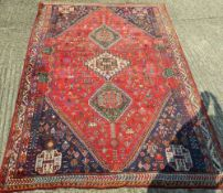 A red ground Persian wool rug. 259 x 185 cm.
