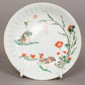 A small Japanese Kakiemon dish Decorated with chickens, butterflies and floral sprays.