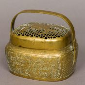 A late 19th century Chinese brass hand warmer Of typical form with pierced removable lid and loop