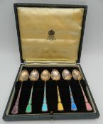 A cased set of silver and enamel spoons.