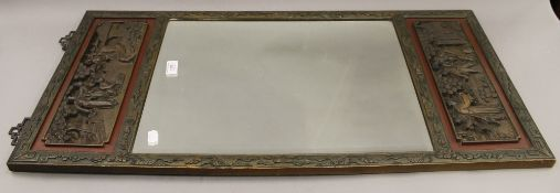 A Chinese carved wooden framed wall glass. 42.5 x 89 cm.