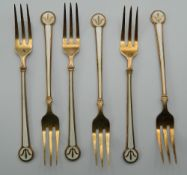 A set of Norwegian enamel decorated silver gilt dessert forks. 13.5 cm long. 106.