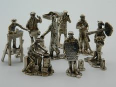 A set of eight silver Cries of London menu holders. The largest 6.5 cm high. 13 troy ounces.