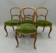A set of four Victorian walnut balloon back chairs. 45 cm wide.