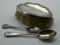 A silver brush and two silver teaspoons.