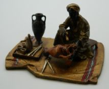 A cold painted bronze model of an Arab painting a pottery vase. 9 cm wide.
