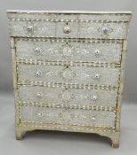 A Syrian mother-of-pearl inlaid chest of drawers with associated marble top.