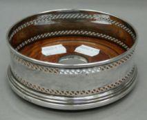 A silver mounted bottle coaster. 12 cm diameter.