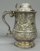 A silver plated lidded tankard, with embossed decoration. 20 cm high.