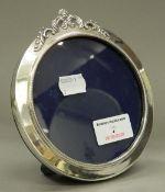 A circular silver photograph frame. 13 cm wide.