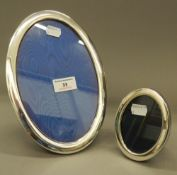 Two oval silver photograph frames. The largest 16.5 cm x 24 cm.