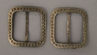A pair of unmarked white metal buckles. Each 5 cm wide.
