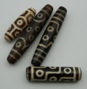 Four agate dzi beads. The largest 7.5 cm long.