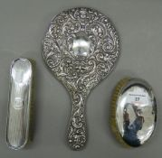 A silver hand mirror and two silver brushes. The former 28 cm high.