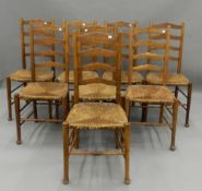 A set of eight early 20th century rush seated ladder back chairs. 43.5 cm wide.