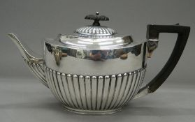 A silver teapot. 28 cm long. 18.9 troy ounces total weight.