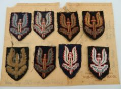A collection of SAS (Special Air Service) beret cloth patches mounted on card,