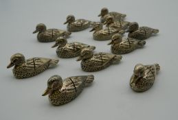 A set of twelve place card holders formed as ducks. Each 4.5 cm long.