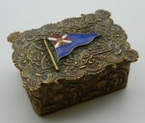 A Victorian brass box, set with an enamel flag. 7 cm wide.