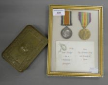 A framed pair of WWI medals awarded to Pte E Fuller of the Suffolk Regiment, a Princess Mary tin,